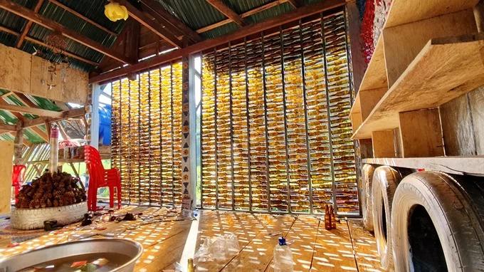 Vách tường của quán được làm từ hàng trăm vỏ chai. Một số trang trí được thiết kế từ những chiếc lá khô chủ quán lấy trong rừng.