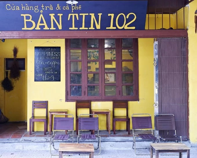 """Bản tin 102 là quán trà và cà phê nằm trong một ngõ nhỏ ở phố Tô Hiệu, quận Cầu Giấy, Hà Nội. Quán mở từ năm 2017, đối diện với tiệm trà thiền đã kinh doanh 10 năm của vợ chồng chủ quán. """"Tên của tiệm thực ra được đặt ngẫu nhiên, giúp thể hiện sự độc nhất của nó và trùng hợp khi số nhà ở đây là 102"""", chị Vân, chủ quán chia sẻ."""