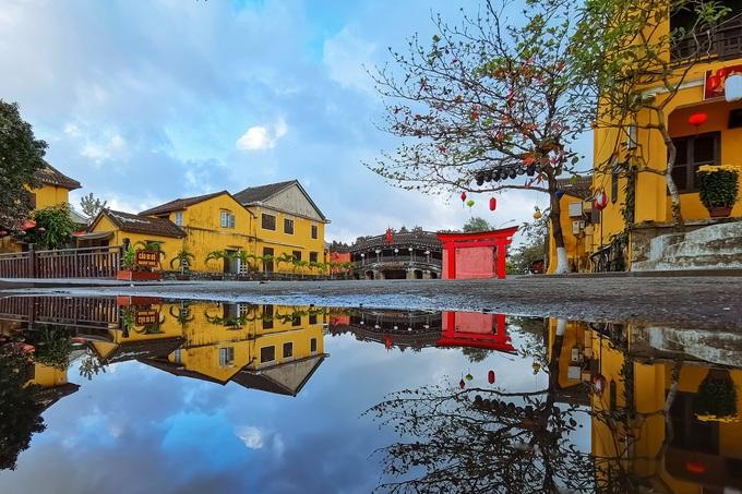 Sau cơn mưa, một số du khách thích ghi lại khung cảnh phố cổ phản chiếu dưới vũng nước, bởi cho góc nhìn mới mẻ.
