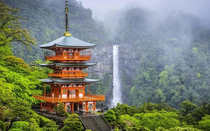 """Chùa Seiganto-ji tọa lạc tại tỉnh Wakayama, cao 3 tầng được xây dựng cạnh thác Nachi 133 m, thác nước đơn có dòng chảy không bị gián đoạn cao nhất Nhật Bản. Seiganto-ji được cho là thành lập vào đầu thế kỷ thứ 5 bởi một nhà sư từ Ấn Độ, là một phần trong di sản thế giới """"Con đường hành hương và thánh địa vùng núi Kii"""" được UNESCO công nhận năm 2004. Ảnh: Besthq Wallpapers."""
