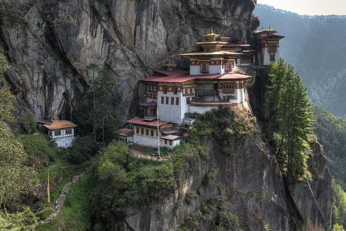 Bhutan có nhiều tu viện và công trình Phật giáo linh thiêng, nổi tiếng. Một trong số đó là tu viện Paro Taktsang xây dựng từ năm 1692, tọa lạc trên một vách đá cao giữa tầng mây nhìn xuống thung lũng Paro. Theo truyền thuyết, ngài Padmasambhava bay đến thung lũng Paro dưới hình dạng hóa thân của thần Dorji Drolo cưỡi trên lưng con hổ cái. Sau đó, ngài đã ngồi thiền suốt ba năm liên tục vào thế kỷ thứ 8 tại 13 hang động, trong đó Paro Taktsang là hang nổi tiếng nhất, nên người dân địa phương còn gọi hang này là Hang Hổ (Tiger Nest). Trên đường dẫn lên tu viện Paro Taktsang, du khách sẽ nhìn thấy làng Lakhang và chùa Urgyan Tsemo tọa lạc trên một khu núi đá khá bằng phẳng. Dọc lối mòn dẫn lên tu viện còn có một thác nước 60 m và đổ vào một hồ thiêng, cuối đường là chính điện của tu viện. Ảnh: Ruminate.