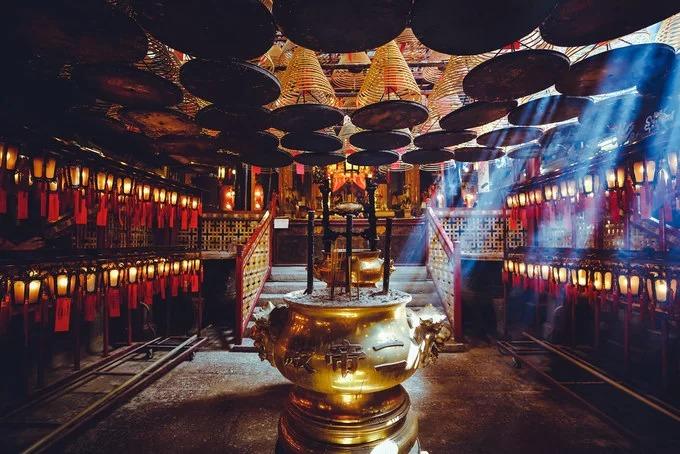Đền Man Mo, Hong Kong được xây dựng vào năm 1847, nhằm tôn vinh Thần Man và Thần Mo. Thần Man là vị thần của văn học, mặc áo màu đỏ và trên tay cầm bút thư pháp. Thần Mo là vị thần chiến tranh, mặc áo màu xanh lá cây và trên tay cầm thanh kiếm. Vào bên trong, du khách sẽ ấn tượng với những khoanh nhang khổng lồ được thả từ trên trần nhà xuống, khói nhang luôn ngập tràn trong không gian. Ngoài ra, trên trần treo những tờ giấy màu đỏ ghi điều ước về thi đậu, học giỏi, gặp mọi sự may mắn trên đường công danh sự nghiệp, cầu làm hòa, giải quyết mọi tranh chấp với nhau. Ảnh: Patrick Foto.