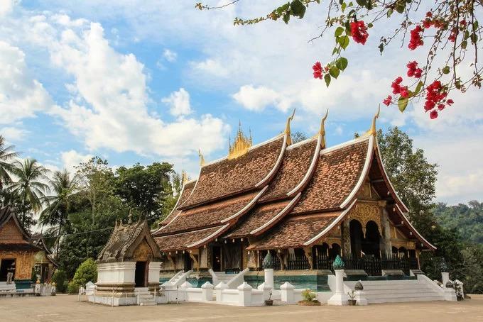 Nằm ở cuối đường Sakkarin, gần với ngã ba tiếp giáp giữa sông Mekong và sông Nam Khan, chùa Wat Xieng Thong được xây dựng năm 1560 dưới thời vua Setthathirat. Đây được xem là một trong những ngôi chùa cổ nhất của cố đô Luang Prabang, Lào. Chùa Wat Xieng Thong có chánh điện mang phong cách kiến trúc đặc trưng của Luang Prabang cổ với mái lợp ba tầng hạ sâu hướng về mặt đất, bao quanh là những miếu đường nhỏ có cùng một lối kiến trúc. Ngoài ra, chùa còn nổi bật với những bức tranh đa sắc màu về lịch sử Phật giáo và lịch sử dân tộc, được các họa sĩ dùng miếng sành, sứ lắp ghép tỉ mỉ lại với nhau hoặc trực tiếp vẽ lên tường, tạo nên các tác phẩm nghệ thuật độc đáo. Ảnh: Maria Globetrotter.