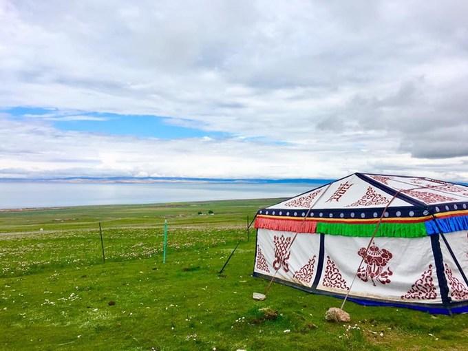 Xe chở du khách lên triền núi để nhìn ra hồ. Ở đó có vài chiếc lều của khách du lịch thuê cắm trại để trải nghiệm đời sống du mục, phía trước là thảm hoa dại, cỏ xanh mơn mởn.