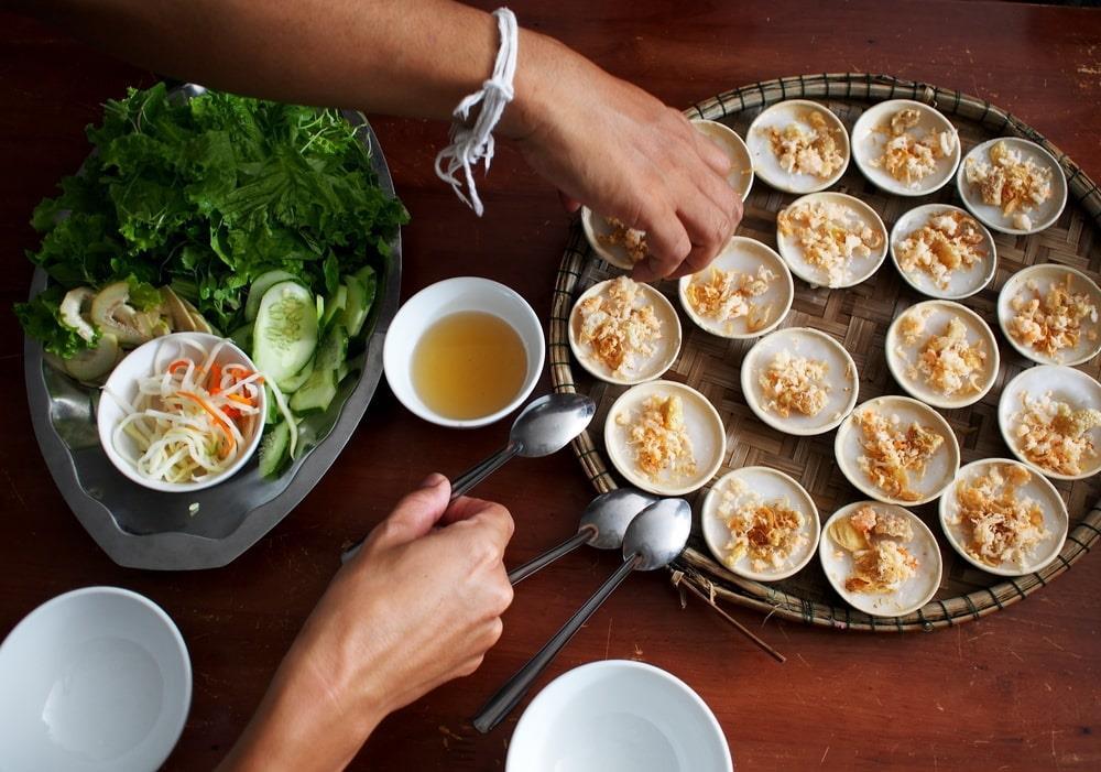 Ăn: Được xếp vào hàng trứ danh của ẩm thực Việt, món Huế thừa hưởng nét tinh túy hoàng tộc từ những đầu bếp đã phục vụ các gia đình vua chúa qua hàng thế kỷ. Dù không ít khách sạn ở Huế tự hào khi sở hữu nhà hàng phục vụ nhiều món địa phương đặc sắc, du khách vẫn nên thử các quán ăn dọc đường để trải nghiệm hương vị đích thực. Ảnh: Chonlawut.