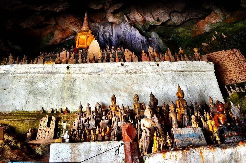 Bạn sẽ cần trang bị một chiếc đèn pin để khám phá hết vẻ đẹp bí ẩn của hang động này. Thời gian tốt nhất để tham quan Pak Ou là buổi chiều bởi các tour du lịch thường đến đây vào buổi sáng. Không gian đông đúc sẽ làm giảm bầu không khí tâm linh của hang động. Ảnh: LandLopers.