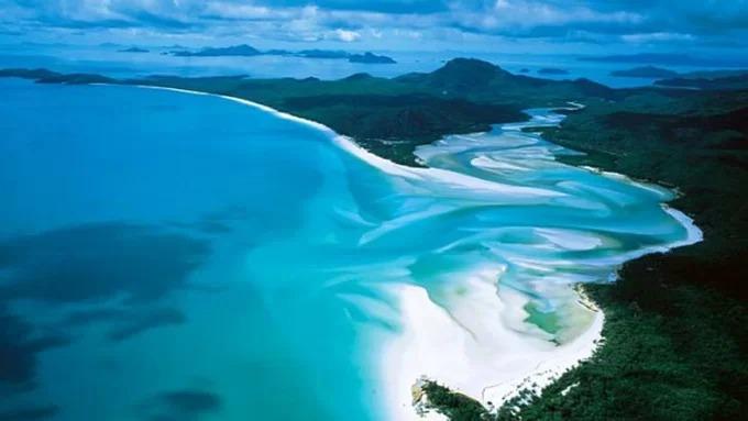 Whitehaven: Nơi cát mềm nhất  Trải dài 7 km dọc theo đảo Whitehaven ở vùng Great Barrier, bãi biển này gồm 98% cát silica tinh khiết, loại cát trắng và mềm mại. Điều đặc biệt nữa là cát ở đây không hề nóng, dù khí hậu Queensland khắc nghiệt.  Du khách có thể đến đây bằng thuyền, dành cả ngày đi bộ trên cát mềm, hoặc lặn trong làn nước biển xanh như ngọc, ngồi thư giãn và nhấm nháp rượu sâm banh dưới hàng phi lao. Ảnh: CNN.