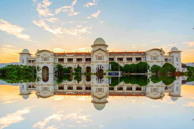 """Tham quan """"tam giác vàng""""  """"Tam giác vàng"""" bao gồm 3 điểm tham quan ở khu vực trung tâm: Ga xe lửa Ipoh, Tòa thị chính và Tòa án thành phố. Hầu hết lối kiến trúc ở đây đều được xây dựng theo kiểu hoàng gia Anh. Nhà ga Ipoh có từ năm 1917, được ví như """"Taj Mahal"""" của Ipoh bởi phong cách nghệ thuật Morocco. Tòa thị chính là địa điểm lý tưởng để du khách chụp ảnh. Cách đó khoảng 5 phút đi bộ là tòa án thành phố mang sắc trắng tinh khôi và tháp đồng hồ khổng lồ Birch Memorial - một trong 24 điểm tham quan trên bản đồ di sản thành phố. Ảnh: airellizwan."""