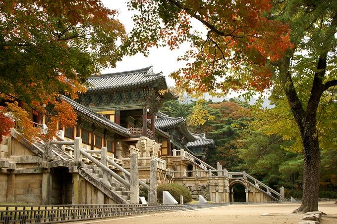 """Chùa Phật quốc Bulguksa  Ngôi chùa tọa lạc trên triền núi thiêng Tohamsan. Cái tên Bulguksa có nghĩa là """"ngôi chùa của nước Phật"""". Chùa xây dựng vào năm 774 của vương triều Silla với kiến trúc độc đáo trông giống như một cung điện. Các hoa văn trang trí trên cột, mái vòm nổi bật với hai màu xanh đỏ mang ý nghĩa tượng trưng cho đất và trời. Đến đây vào mùa thu, bạn sẽ cảm nhận được vẻ đẹp cổ kính ẩn hiện trong không gian lãng mạn. Năm 1995, Bulguksa được UNESCO công nhận là Di sản văn hóa thế giới. Ảnh: MicheleB."""