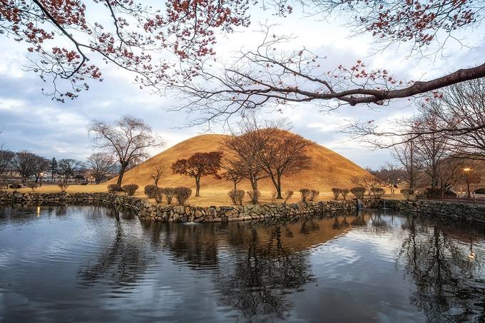 Khu lăng mộ Daereungwon  Daereungwon là quần thể gồm nhiều lăng mộ của các vị vua và hoàng hậu. Nhưng nổi tiếng nhất trong khu di tích lịch sử này là công viên lăng mộ Tumuli - nơi tọa lạc của 23 trong số 200 lăng mộ được tìm thấy ở cố đô Gyeongju. Những lăng mộ như đồi núi thu nhỏ được phủ cỏ xanh tươi vào mùa xuân và ngả vàng khi sang thu. Ảnh: Aaron choi.