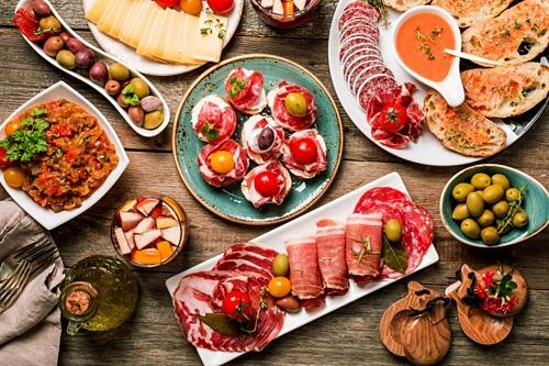 Ngoài các bữa ăn chính, người Tây Ban Nha thường ăn tapas như bữa phụ. Ảnh: Get Your Guide.