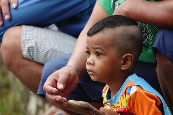Cậu bé Khmer theo cha mẹ đi xem hội đua bò.