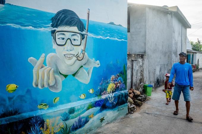 """Cũng khoảng hai năm nay, những bức tường cũ trên đảo đã được thay mới bằng bích họa có chủ đề gần gũi với thiên nhiên, con người như lặn biển, bảo vệ môi trường...  Nếu """"làng bích họa"""" Tam Thanh nổi tiếng ở tỉnh Quảng Nam là sản phẩm của những người bạn Hàn Quốc tặng cho Việt Nam, thì làng bích họa An Bình là sản phẩm của chính những bạn trẻ Việt."""