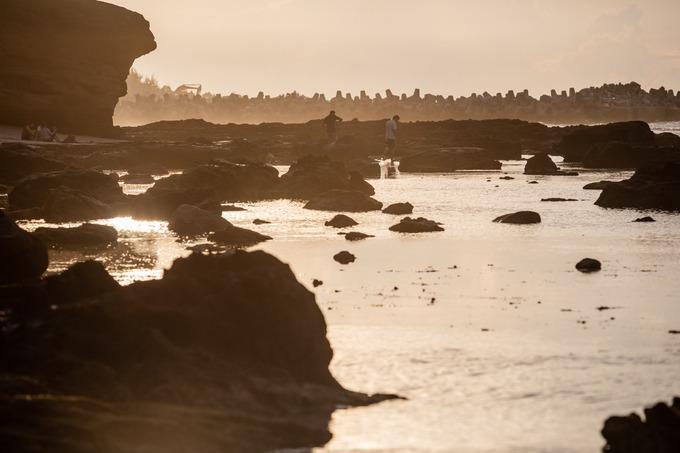 Hoàng hôn xuống, nước triều rút để lộ những dải san hô trước sân chùa cho du khách dạo bộ và ngắm cảnh.