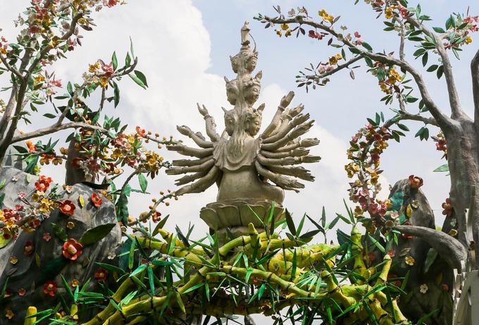 Trên đỉnh cổng chùa bài trí tượng Bồ tát nghìn tay ngồi trên đài sen, bao quanh là những nhành hoa mai, sala.