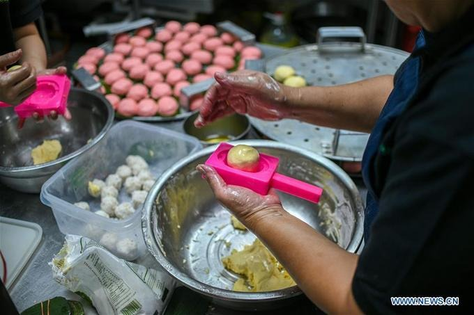 Bánh được vo viên bằng tay, sau đó người làm bánh sẽ ấn vào một chiếc khuôn sẵn. Chiếc bánh in hoa văn hoạ tiết gắn liền với bản sắc dân địa phương.