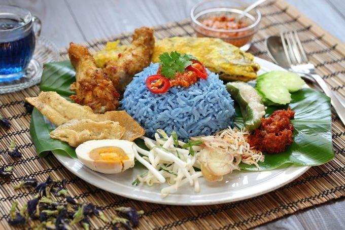 Nasi kerabu  Cơm được nấu từ gạo màu xanh hay còn gọi là gạo thảo mộc. Sau khi nấu chín, cơm thường được ăn kèm cùng trứng muối, nước sốt, cá hồi chiên giòn, gà rán.  Một suất thường được bán với giá khoảng 9 RM (50.000 đồng). Bạn có thể thưởng thức nasi kerabu ở nhà hàng Nasi kerabu Keramat hay Nasi kerabu Kambing Barkar ở thủ đô Malaysia. Ảnh: Shutterstock/Bonchan.