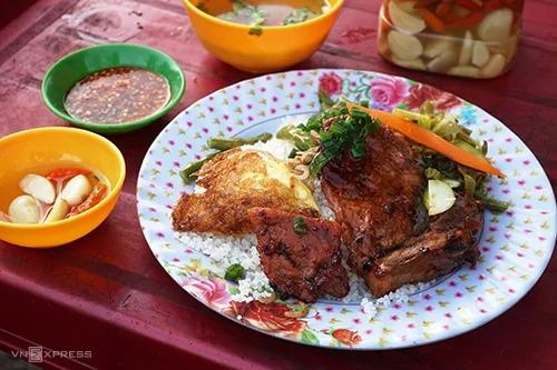 Cơm tấm  Đi dọc các trục đường Lê Lợi, Thủ Khoa Huân hay quanh chợ Châu Đốc, du khách sẽ dễ tìm thấy một quán cơm tấm thơm ngon. Món ăn quen thuộc ở miền Tây, khiến khách thòm thèm bởi vị nước mắm chua ngọt kèm miếng thịt nướng mềm, nêm nếm vừa miệng. Khác với thông thường, đồ ăn kèm của cơm tấm ngoài củ cải ngâm chua, ở Châu Đốc còn có cải ngâm chua, khiến hương vị món trở nên mới mẻ. Cơm ăn chắc bụng nên bạn có thể dùng vào bữa sáng để nạp năng lượng cho ngày mới. Giá mỗi đĩa cơm tấm sườn bì chả khoảng 25.000 - 30.000 đồng.