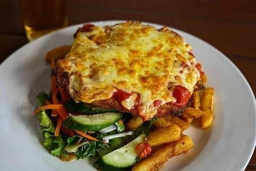 Gà parmigiana xuất hiện lần đầu tiên năm 1980 ở Australia và trở thành món ăn biểu tượng của quốc gia này. Ban đầu nguyên liệu chính của parmigiana là cà tím, sau đó đã phát triển thành gà hầm sốt cà chua với phô mai và giăm bông prosciutto. Món ăn này thường được phục vụ chung với khoai tây chiên trong các quán rượu với giá bán là 6 AUD (gần 100.000 đồng). Ảnh: Irymple Hotel.