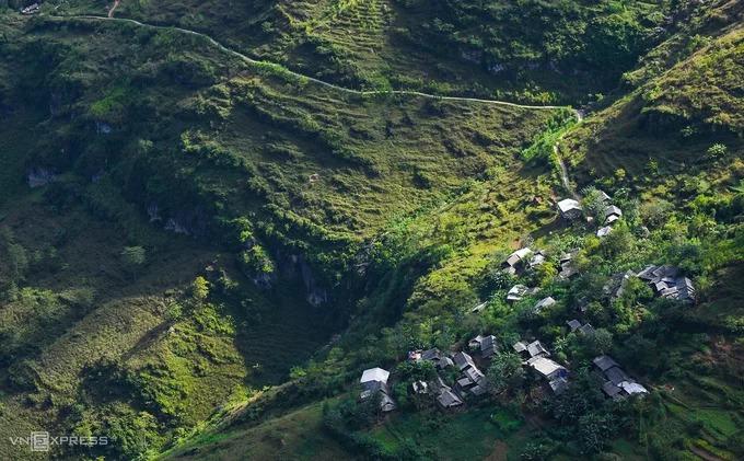 Một bản làng nằm ở triền đèo Mã Pí Lèng trong ánh nắng chiều.