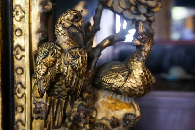 Những chạm trổ rồng phượng, chim công, mai, lan, cúc, trúc... tinh xảo theo văn hóa phương Đông nổi bật ở phòng khách. Màu vàng thể hiện cho sự quyền quý của chủ nhân căn nhà.