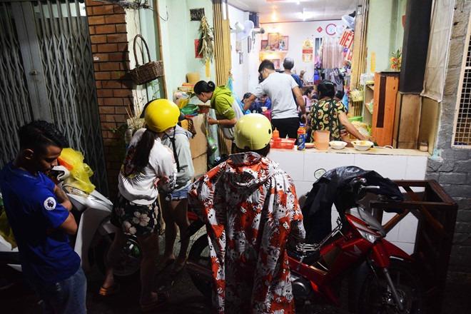 Nhiều người dù mưa vẫn kiên nhẫn đợi để mua được phần ăn mang về ẢNH:HOÀI NHÂN