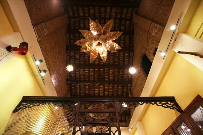Chiếc đèn chùm bằng tre treo trên trần nhà, mái lợp ngói âm dương vẫn được giữ nguyên của ngôi nhà cổ.