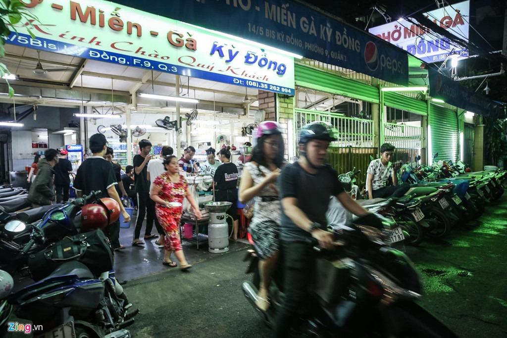 Từ những năm 1975, người dân Sài Gòn đã quá quen với xe hủ tiếu gà rong ruổi khắp quận 3. Khi công việc kinh doanh khấm khá, chủ quán tìm đến con hẻm 14 Kỳ Đồng để xây dựng mặt bằng. Lượng khách ra vào tấp nập kéo theo các quán café và xe trái cây, đồ ăn vặt trong con hẻm nhỏ này.