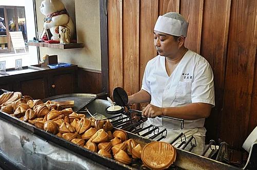 Thợ làm bánh tại tiệm Houkyokudo đang đổ bột vào khuôn. Ảnh: Selena Hoy.