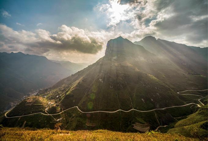 """Đèo Mã Pì Lèng nằm ở độ cao 1.200 m, thuộc cao nguyên đá Đồng Văn, địa danh được UNESCO công nhận là công viên địa chất toàn cầu vào năm 2010. Nhìn từ xa, con đèo như một """"sợi chỉ"""" vắt giữa lưng chừng đồi núi tạo nên khung cảnh hùng vĩ của cao nguyên núi đá."""