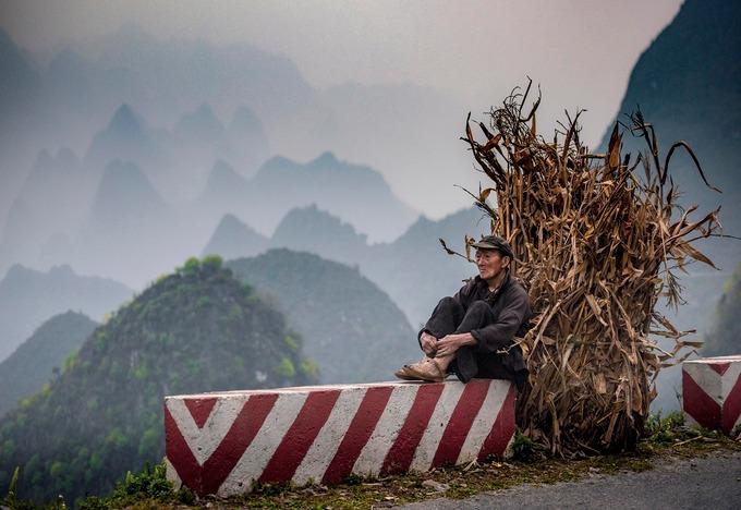 Ngoài chiêm ngưỡng phong cảnh, du khách có thể tìm hiểu và thử trải nghiệm cuộc sống của người dân bản địa trên đèo Mã Pì Lèng. Trong ảnh là một người dân tộc Mông ngồi nghỉ trên đường gùi bó cây ngô khô về nhà.