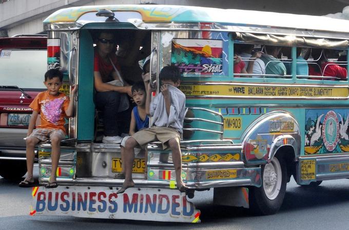 """Những chiếc """"jeepney"""" phỏng theo xe jeep Mỹ thời Thế chiến II chạy trên đường phố là hình ảnh đặc trưng của Philippines. Phương tiện này phổ biến với người dân thuộc tầng lớp trung lưu hoặc thấp hơn bởi giá vé chỉ khoảng 8 peso (4.000 đồng). Xe không có lộ trình cố định, vì vậy hành khách chỉ cần nhảy lên một chiếc jeepney chạy theo hướng cần đến, đưa tiền cho tài xế và rung chuông khi họ muốn xuống xe.  Xe jeepney là điều đáng tự hào của nhiều người Philippines. Tài xế thường vẽ những hình tôn giáo hoặc hoa văn phức tạp lên xe và mở nhạc lớn. Hiện có khoảng 50.000 xe jeepney chạy hàng ngày chỉ riêng ở Manila. Nhưng biểu tượng của Philippines lại góp phần gây ô nhiễm không khí và nguy hiểm cho giao thông, bởi những chiếc xe cũ nhả ra khói đen đặc còn tài xế thường phanh gấp khi trả khách. Từ 2018, Tổng thống Rodrigo Duterte tuyên bố chính quyền sẽ từng bước loại bỏ xe jeepney trên đường phố, New York Times đưa tin. Ảnh: AFP."""