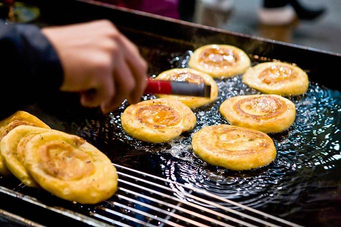Bánh rán Hàn Quốc (hotteok)  Những chiếc bánh rán chứa một loại siro ngọt hoặc nhiều loại nhân khác nhau như mật ong, hạt dẻ..., và được lăn trong đường sau khi rán chín. Không những ngon, mà vẻ ngoài của bánh cũng rất đẹp. Bánh rán với vỏ ngoài nóng hổi, nhân bên trong ngọt ngào sẽ giúp chuyến đi chơi của bạn ấm áp hơn rất nhiều. Ảnh: Visit Korea.