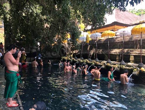 Du khách tắm rửa để tẩy trần tại dòng nước thiêng ở đền suối thiêng Tampak Siring Holy Water Spring.