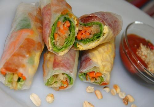 """Bò bía  Đây là món quà vặt dễ ăn, dễ tìm, giá thành phải chăng được người Việt ưa chuộng. """"Bò bía"""" là từ mượn của tiếng Hoa vùng Phúc Kiến. Tại Sài Gòn, bò bía mặn phổ biến hơn loại ngọt. Trong đó gồm các thành phần như lạp xưởng, trứng tráng, cà rốt, rau xà lách, củ sắn (miền Bắc gọi là củ đậu) hoặc su hào, tôm khô, rau thơm... Tất cả được xắt nhỏ và cuộn trong tấm bánh tráng làm từ bột mì. Tương ớt xí muội có vị chua ngọt, trộn với đậu phộng rang giã nhỏ phi bằng dầu ăn, hành khô là sốt chấm được yêu thích. Một cuốn bò bía có giá 1.000 - 5.000 đồng.  Địa chỉ gợi ý: Khu cư xá Lữ Gia (quận 11), đường Nguyễn Văn Giai (quận 1), chợ Tân Định (quận 1), đường Sương Nguyệt Ánh (quận 1), đường Trần Bình Trọng (quận 5). Ảnh: Khánh Hòa."""