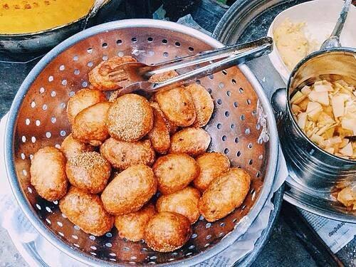 Bánh rán mặn  Quán bánh thường mở cửa lúc xế chiều, nằm trong một kiot nhỏ nên không có nhiều chỗ ngồi. Khách tới đây thường ngồi sang các hàng bên cạnh hoặc mua mang đi. Bánh rán có 2 loại ngọt vừng và nhân thịt mặn. Cả 2 đều được thực khách đánh giá là ngon với bột bánh dẻo thơm mà không bị chua. Sau khi chiên ngập dầu, lớp vỏ ngoài giòn rụm và không ngấm mỡ. Không giống bánh rán mặn phủ sốt ở Lạc Long Quân, bánh ở đây được ăn kèm với rau sống, nước chấm chua ngọt và đu đủ muối. Mỗi chiếc bánh có giá 5.000 đồng. Ảnh: Trang Nhim Tron.