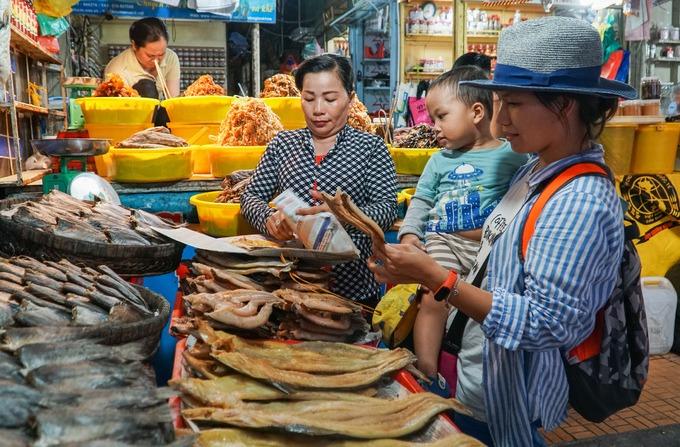 """Chị Kim Ngân (phải), đến từ Hà Nội, ghé chơi chợ Châu Đốc trong chuyến du lịch miền Tây. """"Các loại mắm và khô ở chợ rất phong phú, trình bày bắt mắt và rẻ hơn nơi khác"""", chị Ngân nói khi đang chọn mua khô cá về làm quà."""