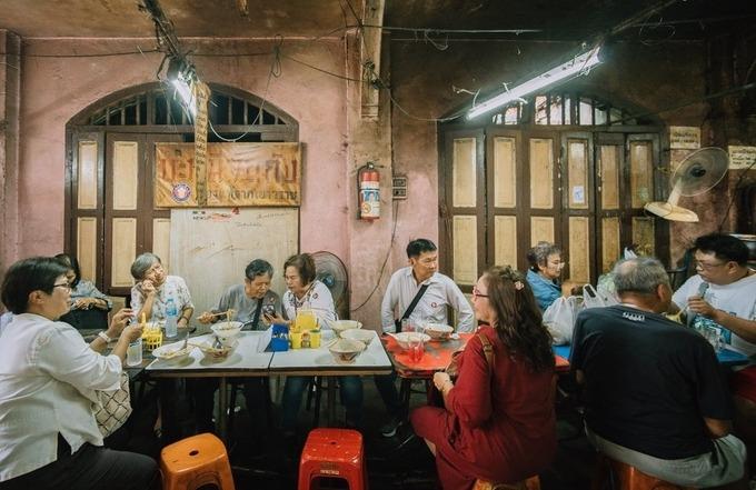 Bạn đến ga tàu điện Wat Mangkon, đi theo hướng vào chợ cũ, sau đó hỏi thăm để tìm đến quán. Trước kia, chỉ người trong chợ đến ăn. Từ khi nhận được sự quan tâm của nhiều du khách, quán khá đông vào giờ cơm trưa hay chiều. Phục vụ nhanh nhẹn, bạn không phải đợi lâu. Quán đóng cửa vào ngày 15 và 30 hàng tháng.