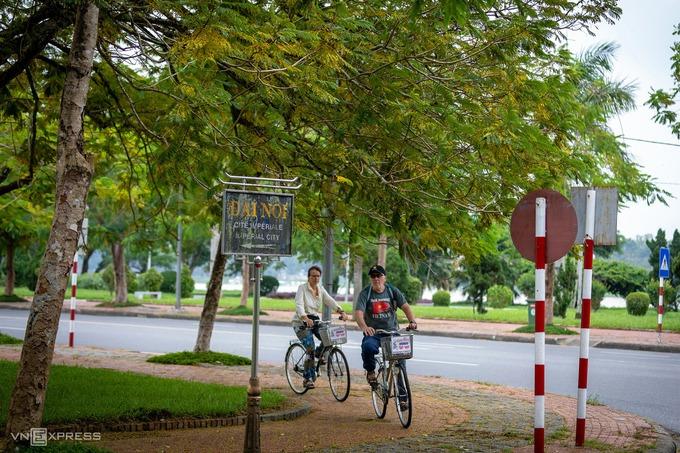 Hai du khách nước ngoài thư thả đạp xe trên đường Trần Hưng Đạo hướng về phía Đại nội Huế trong khung cảnh lá vàng mùa thu.