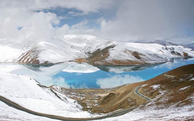 """Hồ Yamdrok  Với diện tích 638 km2, Yamdrok là một trong ba hồ thánh ở Tây Tạng, nằm ở quận Nagarzê, tỉnh Shannan và cách thành phố Lhasa khoảng 70 km. Yamdrok có nghĩa là """"hồ ngọc"""" trong tiếng Tây Tạng, nổi tiếng bởi màu lam. Ảnh: Make My Trip."""