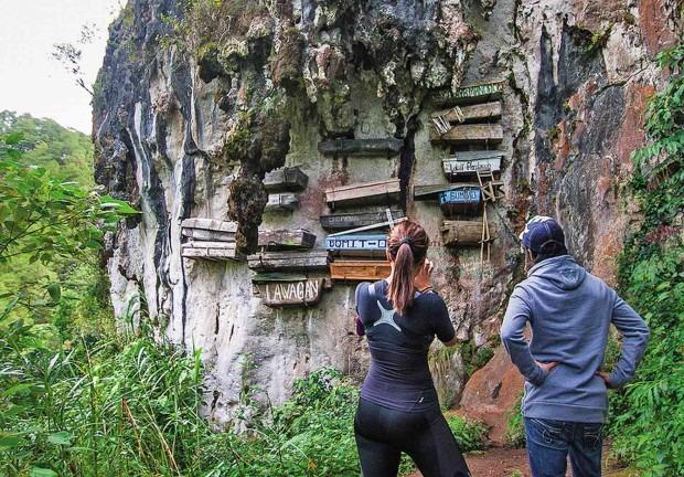 """Khám phá thung lũng """"quan tài treo"""": Thung lũng Echo ở vùng núi Sagada, Philippines nổi tiếng với những """"quan tài treo"""" kỳ lạ. Qua nhiều thế kỷ, người Igorot trong vùng đã thực hiện nghi thức chôn cất những người chết trong những chiếc quan tài được treo lơ lửng dọc vách đá. Thung lũng Echo không chỉ mang lại cảm giác hồi hộp cho những ai đặt chân đến đây mà còn khiến người ta đôi chút sợ hãi, rùng mình trước không khí ảm đạm và ma mị. Ảnh: Straightspeak."""