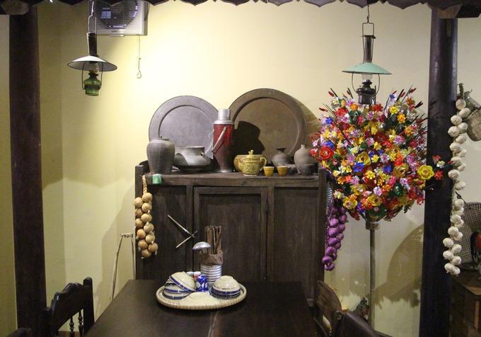 Một góc bàn gợi cho du khách về những căn nhà xưa với chạn bếp, mâm đồng, tỏi treo, hoa giấy trang trí.