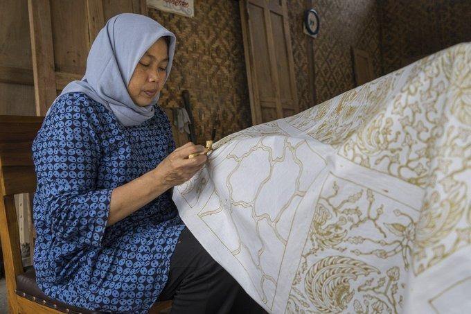 """Du khách tới làng Giriloyo ở vùng Yogyakarta sẽ trông thấy những phụ nữ chăm chú vẽ họa tiết cầu kỳ lên bức vải trắng, bên cạnh là chiếc bếp nhỏ đặt chiếc bát chứa sáp ong nóng chảy. Họ đang làm batik, loại vải nhuộm sáp nổi tiếng của Indonesia, được UNESCO công nhận là di sản văn hóa phi vật thể của thế giới từ năm 2009.  Imaroh, 51 tuổi là một nữ nghệ nhân lâu năm ở làng, gắn bó với công việc từ khi 10 tuổi. Giống với Imaroh, hầu hết phụ nữ trong làng làm batik gần như cả cuộc đời. """"Tôi là thế hệ thứ ba làm batik. Đến nay, con gái tôi cũng đang theo đuổi công việc này"""", Imaroh nói."""