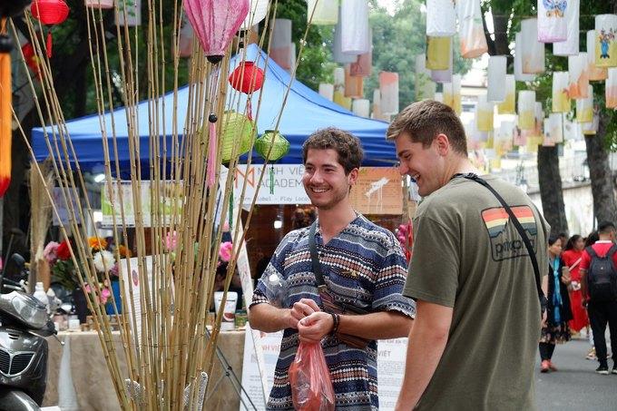 """David (trái) và Patrick (phải), du khách Đức cho biết họ đã phát hiện ra con phố khi đi bộ tham quan. Khi đến Việt Nam, du khách đã biết về Tết truyền thống và khu phố trưng bày nhiều sản phẩm giúp họ tìm hiểu rõ hơn vào dịp lễ.  David chia sẻ: """"Khu phố trưng bày nhiều sản phẩm đẹp, đặc biệt là các cây trang trí trong nhà. Tôi thấy loại cây này (cây quất) giống với họ cam, chanh nhưng nhỏ và đặc biệt hơn"""". Anh cho biết thêm, chỉ một số gian hàng có bảng thuyết minh bằng tiếng Anh, nên họ không hiểu được hết ý nghĩa của các đồ trang trí ở đây."""
