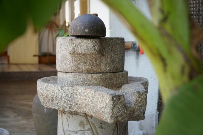 """Chiếc cối đá, dụng cụ xay bột thời xưa, được chủ quán sưu tầm và trưng bày gần gian bếp. """"Tôi đã sưu tầm cối đá, lu nước và gáo dừa ở các huyện gần TP Quy Nhơn"""", anh Tuấn cho biết."""