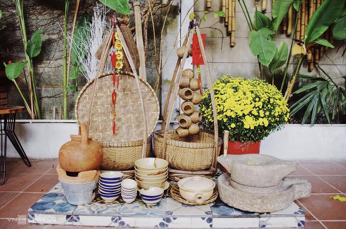 Bên cạnh các tiểu cảnh chủ đề Tết, quán còn trưng bày những hiện vật dân dã, phù hợp với phong cách quán. Chủ quán thiết kế một góc bếp trong khuôn viên, với chiếc cối đá là vật không thể thiếu để xay bột làm mì Quảng.