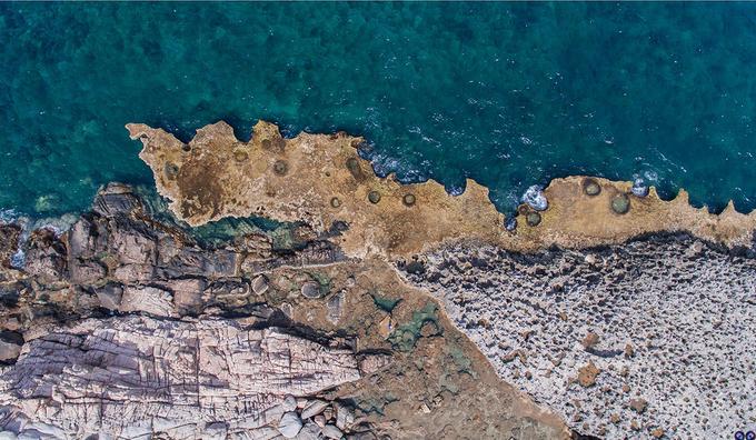 Nhìn từ trên cao, bãi san hô cổ Hang Rái hiện ra với bề mặt gồ ghề và nhiều hang hốc. Theo người dân địa phương, có hai cách lý giải cho tên gọi của địa danh này, một là khi xưa nơi này có nhiều rái cá sinh sống, hai là ở đây có nhiều cây rái dùng để chiết lấy dầu sơn chống thấm cho tàu thuyền. Ảnh: Đặng Thanh Tùng.