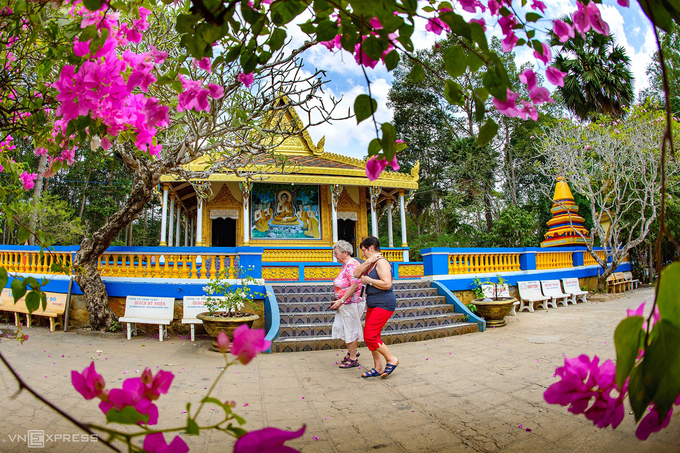 Hai du khách nước ngoài đi ngang qua mặt tiền chánh điện chùa Dơi hôm 16/2. Do ảnh hưởng của dịch bệnh, lượng khách đến chùa giảm so với trước đây.