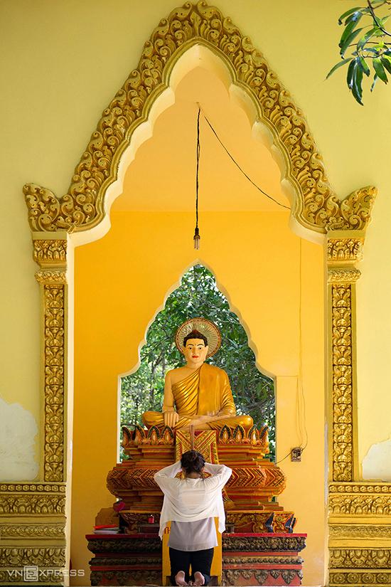 Nữ du khách đang cầu nguyện trước tượng Phật Thích Ca bên ngoài chánh điện chùa. Pho tượng này làm bằng đá nguyên khối cao 1,5 m, ngự trên một tòa sen cao. Xung quanh tượng trang trí các hoa văn, họa tiết đặc trưng của người Khmer.