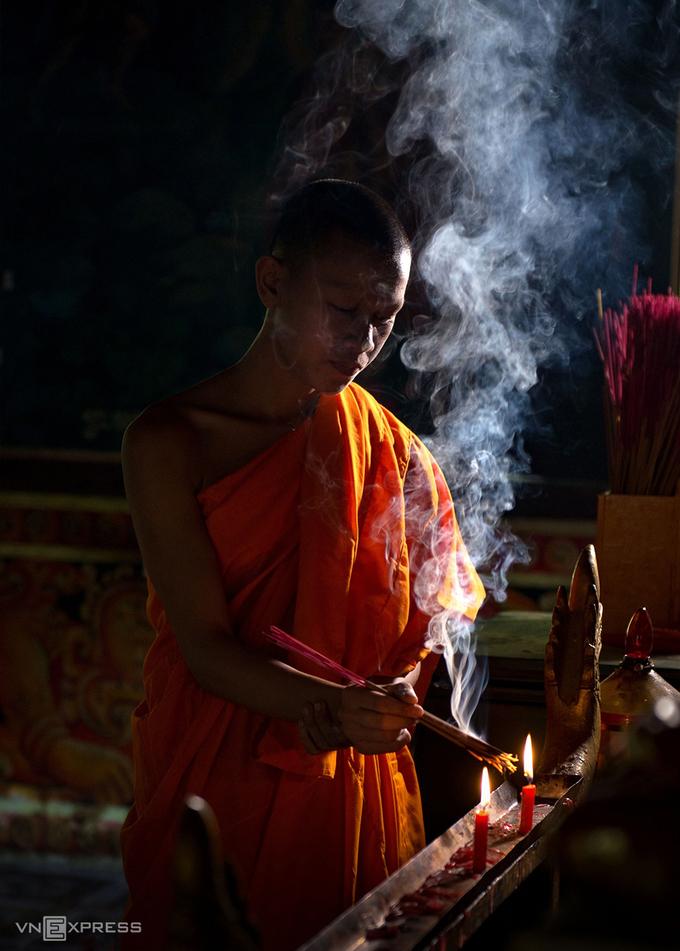 Một vị sư thắp hương trong không gian yên bình của ngôi chùa.